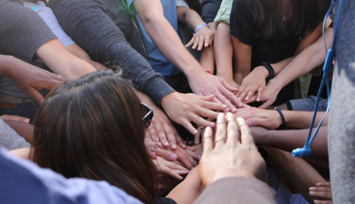 hands reaching in for a huddle
