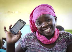 Tala customer holds up smart phone with Tala app on the screen